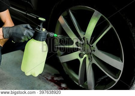 Car Rims Cleaning, Car Detailing Wash Concept. Cropped Close Up Photo Of Male Hand In Black Rubber G