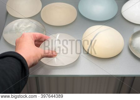 Female Hand Touching Silicone Implants For Breast Augmentation. Cosmetic Plastic Surgery. Demonstrat