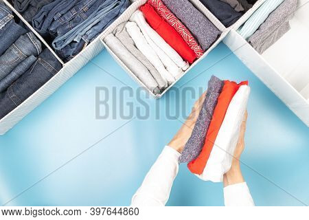 Woman Hands Folds And Puts Clothes To Baskets. Vertical Storage Of Clothing, Tidying Up, Declutter,
