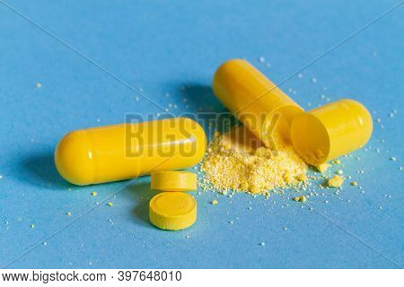 Yellow Capsules With Medicine, From The Capsule Poured Powder. Pills On A Blue Background.
