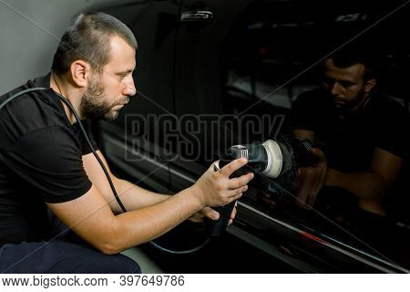 Auto Detailing Service, Polishing Of The Car. Side View Of Young Caucasian Man Worker, Polishing Doo