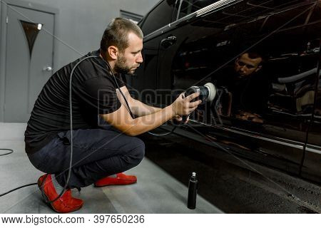 Auto Detailing Service, Polishing Of The Car. Side View Of Young Man Worker In Black Clothes, Polish