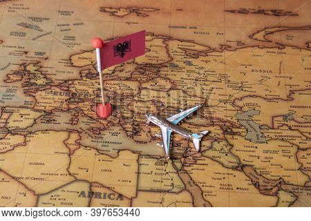 Flag Of Albania And Plane On The World Map.
