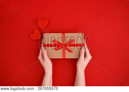 Females Hands Holding Gift Box With Hearts Decoration On Red Background. Christmas, New Year, Valent