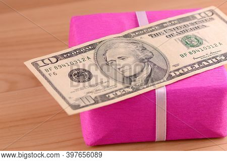Dollars Money Along With A Gift, A Symbol Of The Crisis, Venality, Hoarding And Wealth. American Mon