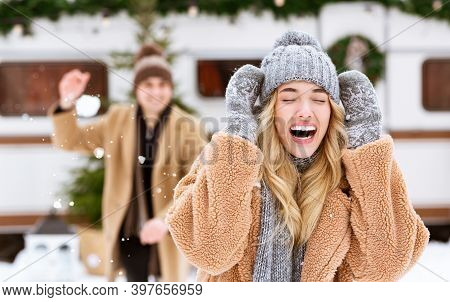 Outdoor Fun. Happy Cheerful Young Couple Throwing Snowballs At Each Other, Having Fun During Winter
