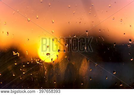 Blurred Background Of Water Droplets On A Dirty Glass Window At Sunset. Look Out The Dirty Window. C