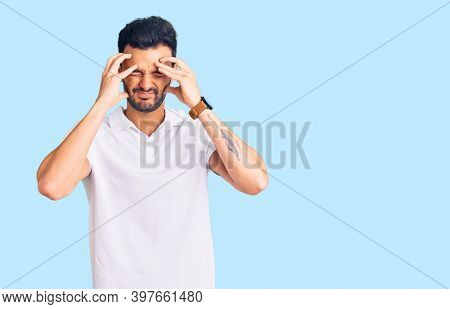 Young handsome hispanic man wearing casual clothes suffering from headache desperate and stressed because pain and migraine. hands on head.