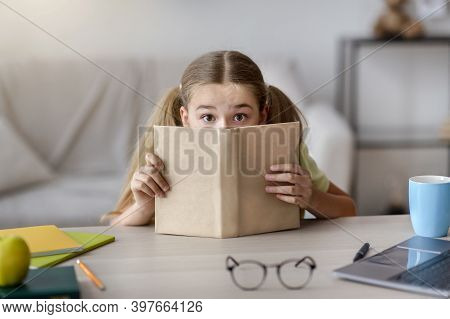 Exam Time And Homework. Portrait Of Scared Girl With Wide Open Eyes Hiding Her Face Behind A Book, S