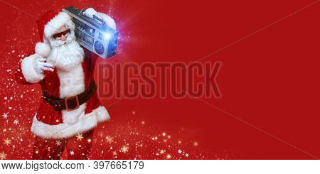 Cool DJ Santa Claus in sunglasses holds tape recorder on a festive background with lights and snowflakes. Christmas songs and music. New Year party. Copy space.