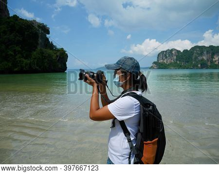 A Woman Wearing Surgical Face Mask Taking Photos On Railay Beach In Thailand