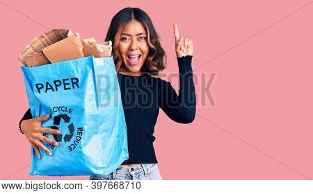 Young beautiful mixed race woman holding recycling wastebasket with paper and cardboard surprised with an idea or question pointing finger with happy face, number one