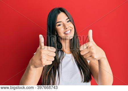 Young brunette woman wearing casual white tshirt over red background approving doing positive gesture with hand, thumbs up smiling and happy for success. winner gesture.