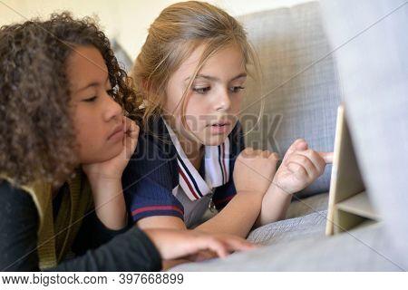 10-year-old girlfriends watching movie on digital tablet