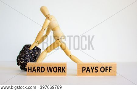 Hard Work Symbol. Wooden Blocks With Words 'hard Work Pays Off'. Wooden Model Of Human With Black St
