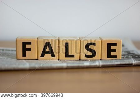 False In News Symbol. Cubes Placed On A Newspaper Form The Word 'false'. Beautiful Wooden Table. Whi