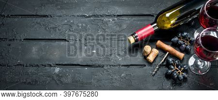 Wine Background. Red Wine With Grapes And Corkscrew. On A Black Rustic Background.