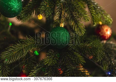 Beautiful Christmas Tree With Green Toy On Branches Close Up. Concept Of A New Year Atmosphere And F