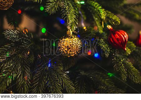 Beautiful Christmas Tree With Red And Gold Toys On Branches Close Up. Concept Of A New Year Atmosphe