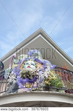 Mardi Gras Mask And Decorations On A Balcony Of A Building In New Orleans French Quarter