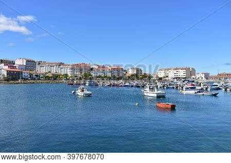 Portosin, Spain. Jun 30, 2020. Harbour And Coastal Village With Galician Fishing Vessels, Rowboats A