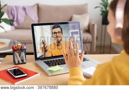 Little Girl Using Headphones And Laptop For Learning Online Class From School Teacher By Remote Inte