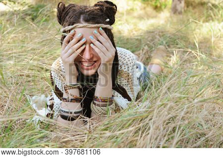 Joyful indie style woman with dreadlocks hairstyle, have a fun closing her face with a hands, sunny autumn outdoor