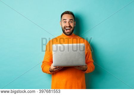 Happy Man Using Laptop And Looking Excited At Camera, Standing With Computer Against Light Blue Back
