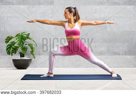 Full Length Portrait Of Young Woman In Sportswear Doing Warrior Yoga Pose At Home.