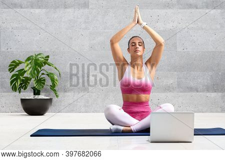 Close Up Portrait Of Young Woman At Yoga Practice. Girl Doing Online Yoga Session At Home In Front O