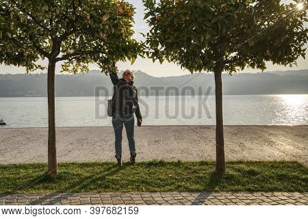 A Middle Aged Caucasian Woman Reaching For A Fruit Of An Orange Tree On The Shore Of The Garda Lake
