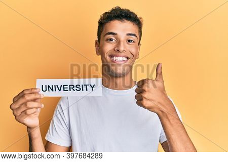 Young handsome african american man holding paper with university word smiling happy and positive, thumb up doing excellent and approval sign