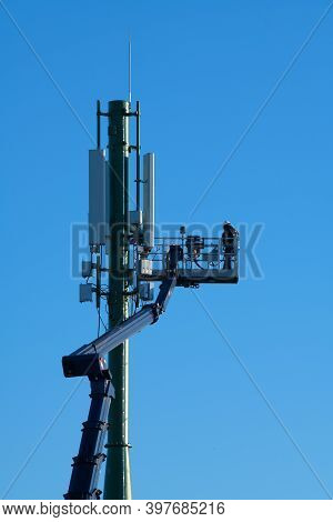 Telecommunications Tower With 4g, 5g Transmitters, Worker On Cellular Base Station With Transmitting