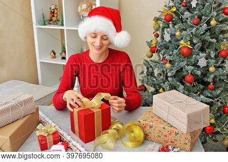 A Girl In A Santa's Helper Hat And A Respiratory Protection Mask And Gloves Is Packing Gifts In Red