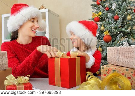 A Mother With Her Daughter In Santa Hats Packs A Gift And Ties A Bow On A Red Gift Box Before The Ch