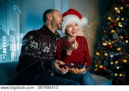 A Husband And His Wife Enjoy Popcorn On Christmas Eve And Laughing Loudly While Watching Movies