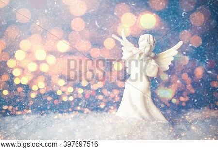 Christmas Angel Figurine And Blur Christmas Lights Stock Photo