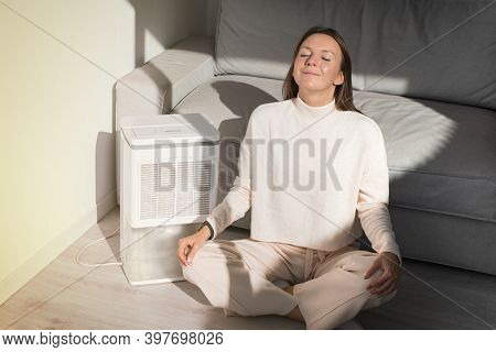 Happy Calm Woman With Closed Eyes Sitting Near Air Purifier And Resting At Home. Relaxing And Breath