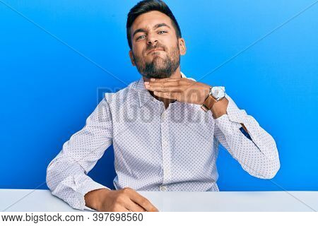 Handsome hispanic man wearing business clothes sitting on the table cutting throat with hand as knife, threaten aggression with furious violence