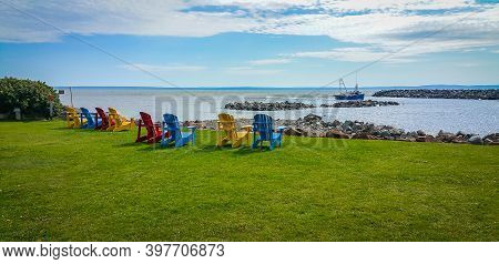 Colorful Wooden Chairs In The Fundy National Park Located On The Bay Of Fundy, Near The Village Of A