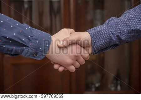 Two Men In Shirts Shake Hands In The Office. Concept: Conclusion Of A Deal Or Contract, Strong Hands