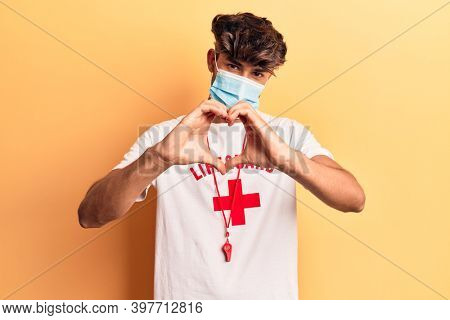 Young hispanic man wearing lifeguard t shirt using medical mask smiling in love doing heart symbol shape with hands. romantic concept.
