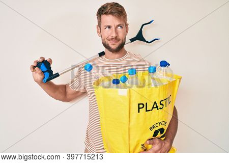 Young caucasian man holding recycling bag with plastic bottles and waste picker smiling looking to the side and staring away thinking.