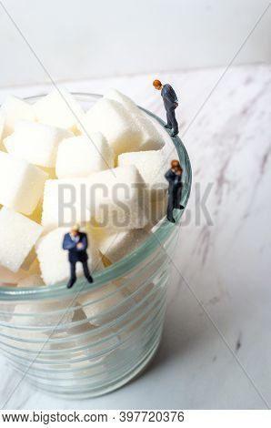 Conceptual Sugar Cubes In Glass And Businessmen Diabetes Conceptual Metaphor