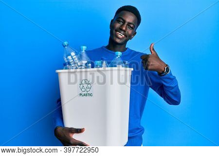 Young african american man holding recycling wastebasket with plastic bottles smiling happy and positive, thumb up doing excellent and approval sign