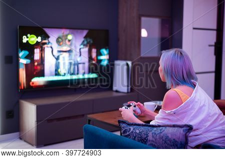 Teenager Girl With Colorful Blue And Pink Hair Hold Joystick And Play Video Games At Home At Night.