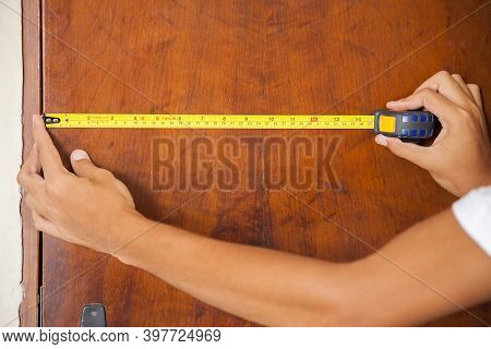 Measuring The Home Door. Wooden Door Being Measured By A Man Using A Measuring Tape. Hands And Arms
