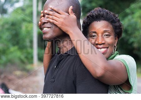 Happy Young Woman In Love Hides The Eyes Of Her Fiance With His Hands