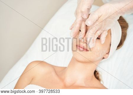 Beautiful Portrait On White Background. Cosmetology Massage. Young Woman Facial Medical Treatment. S