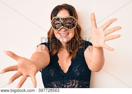 Young beautiful caucasian woman wearing venetian carnival mask looking at the camera smiling with open arms for hug. cheerful expression embracing happiness.